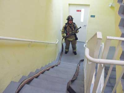 (12) A 100-foot hose bundle is split into two 50-foot stacks that will play hose from the top as firefighters stretch up stairs to the floor above the fire and then back down to the fire floor. (Photos by Chris Martinez.)