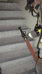 (22) The nozzleman sets the nozzle down on the stairs above him so he doesn't bury it with the hose he pulls to the second-floor landing.