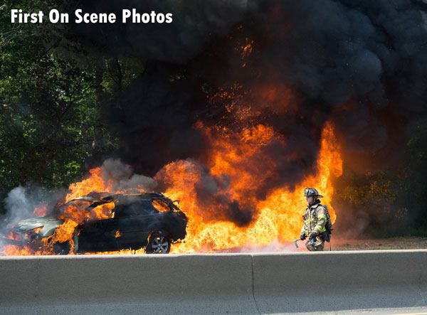 Flames from a car fire rage behind a firefighter responding to the scene.