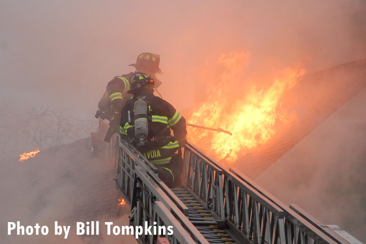 Firefighters perform vertical ventilation at the scene of a fatal house fire in Little Ferry, New Jersey.