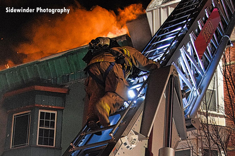 A firefighter on an aerial ladder at the scene of a massive fire in the city of Troy, New York.