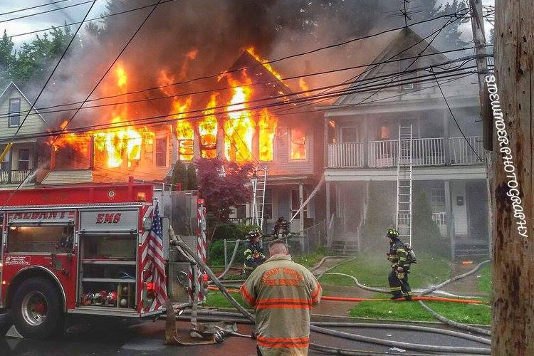Firefighters at the scene of a fire extending through multiple homes in Albany, New York