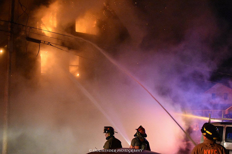 Firefighters train hosestreams through the windows of a burning residence