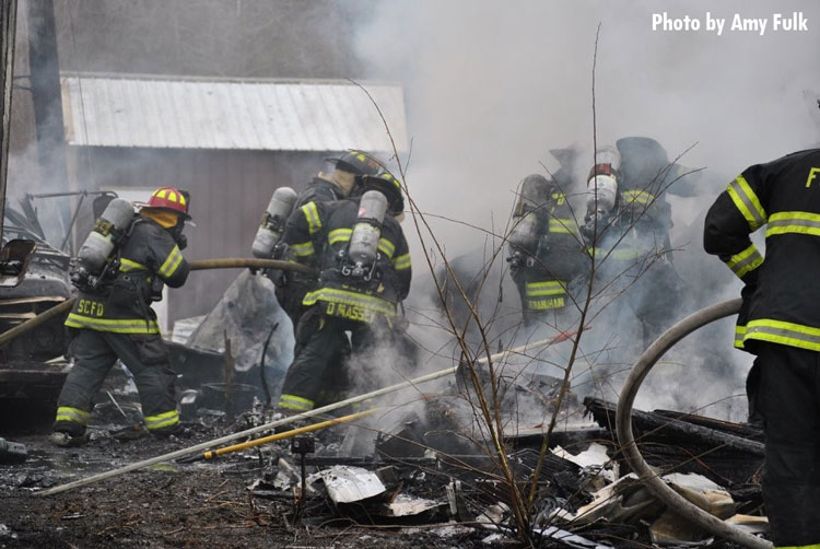 Firefighters perform overhaul after trailer fire