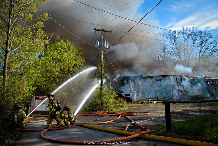 Firefighters work at the scene of a large industrial fire