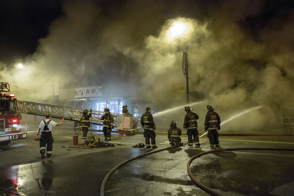 Firefighters operate hoselines at a fire scene.