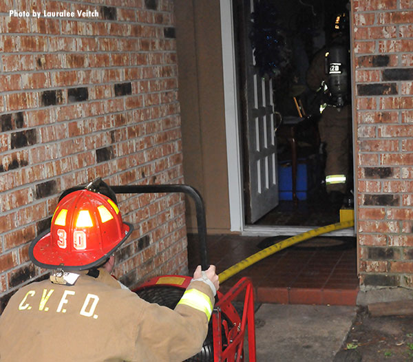 Community Volunteer Fire Department member operates a ventilation fan at the door of a fire scene.