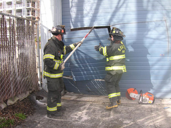Firefighters force entry on a roll-up door during a training evolution.
