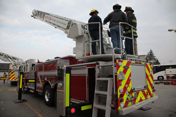 Firefighters on the back of an aerial device.