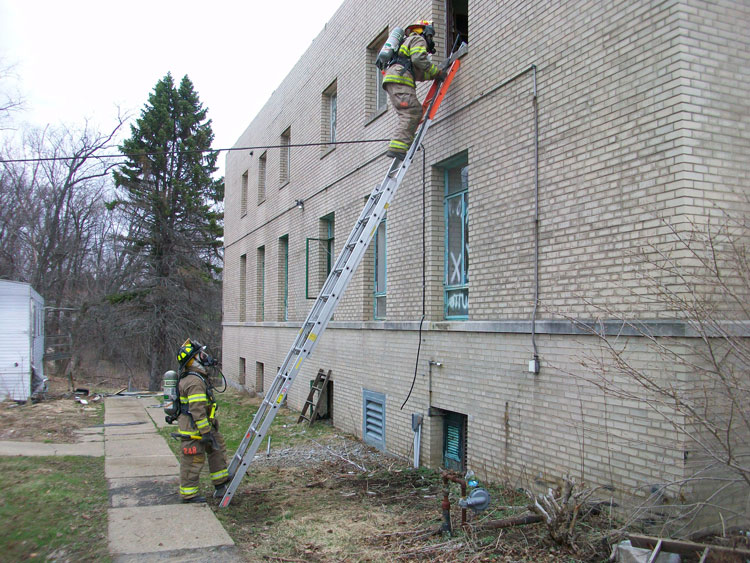 Firefighters ascend a ladder
