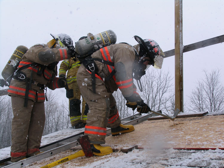 Firefighter uses halligan to cut vent hole