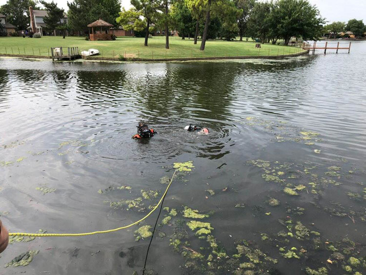 Fire department divers operate in a pond