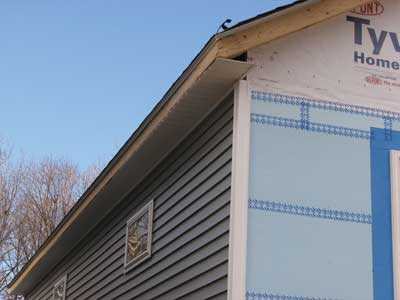 The soffit on the load-bearing side is open and covered with vented vinyl siding to allow air in