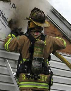 Water is applied from a ground ladder using a 1¾-inch handline from the gable end of the attic to knock down the fire.