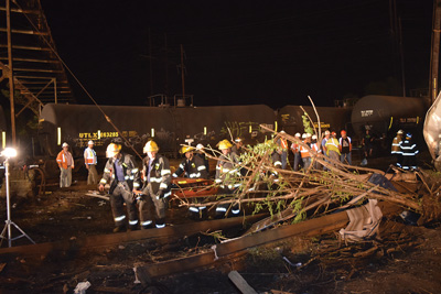 (11) A ladder company used stokes baskets to carry extrication tools to the scene. Responders used stoke baskets with backboards to ferry passengers to the two triage/treatment areas (East and West). Note the close proximity of the stored tank cars to the passenger train wreckage.