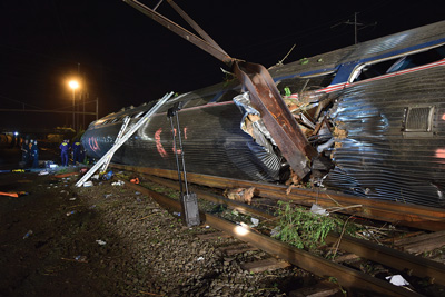 Car 2 lies on its side. A catenary pole penetrated its stainless-steel body. Portable battery-powered LED lighting illuminates the scene. Responders used numerous portable ladders to access the windows of each of the four overturned rail cars. Portable generators and hydraulic extrication equipment are staged outside the car.