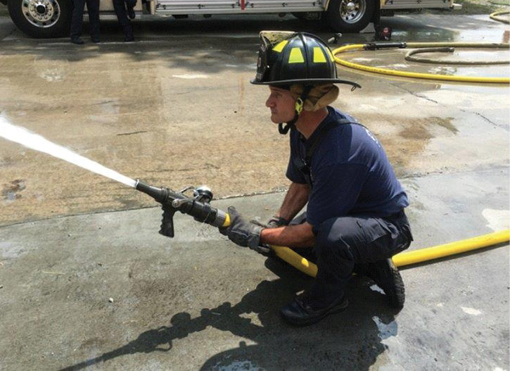 This firefighter is managing a hose and nozzle combination that matches.