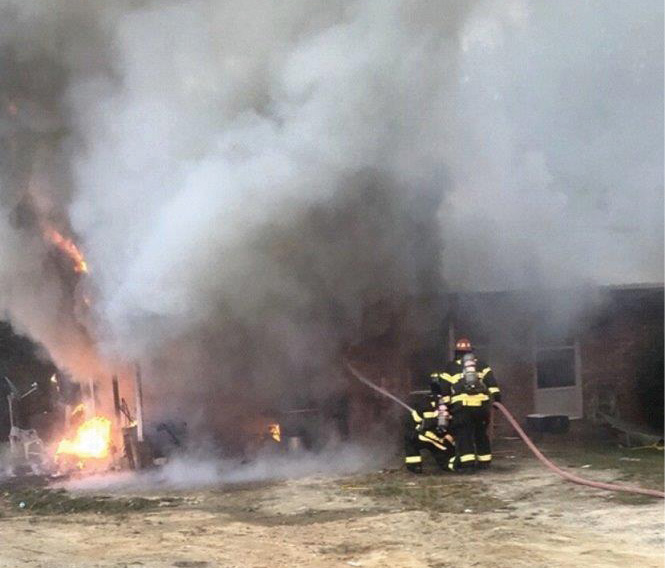 (4) In a rural setting, initial companies will be operating on their own. Hoseline position is extremely critical. Here, the engine crew was able to get a quick knock on this fire in a carport and then reposition the hoseline to the interior. (Photo by Clark McVey.)