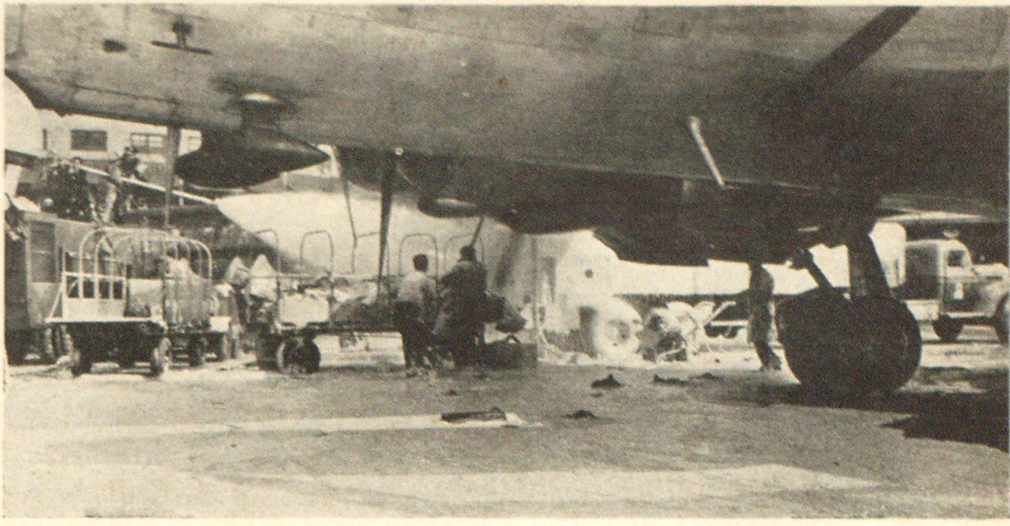 Firemen Using Fog-Foam Prevent Re-Kindle in Tanker Fire Turret pipe with large fog-foam nozzle (left rear) and hand line (right center) operating on rear of tanker as spreading fire is controlleed. View is taken from under side of exposed DC-6 plane which was being loaded with passengers and gas at time. Note extent of foam patter.