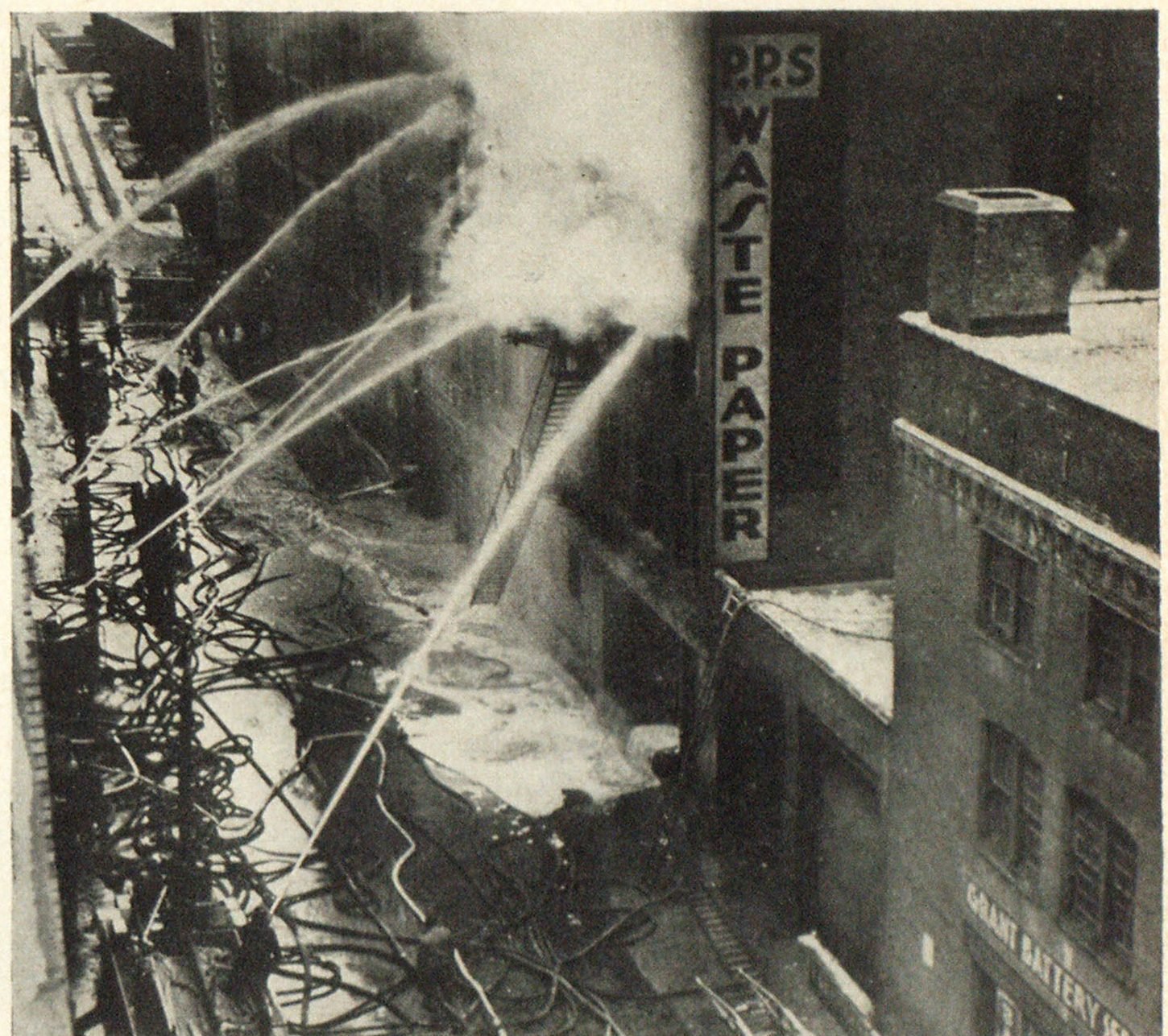 "Pittsburgh Firemen Get Water on Threatening Fire After Delay Firemen under Chief William Davis beginning to get heavy streams on blaze that gutted two buildings, and threatoned downtown Triangle"" area when large water main broke."