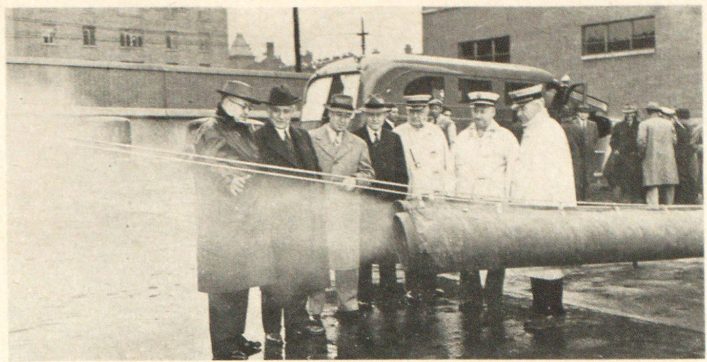 The Lamb Air Mover as a smoke ejector. Former Captain Edward Lamb of the San Francisco Fire Department, inventor of the Lamb Air Mover used on the Airmatic Task Unit of the Cincinnati Fire Department, demonstrates his smoke remover before Cincinnati Fire Chief Barney Houston and other officials.
