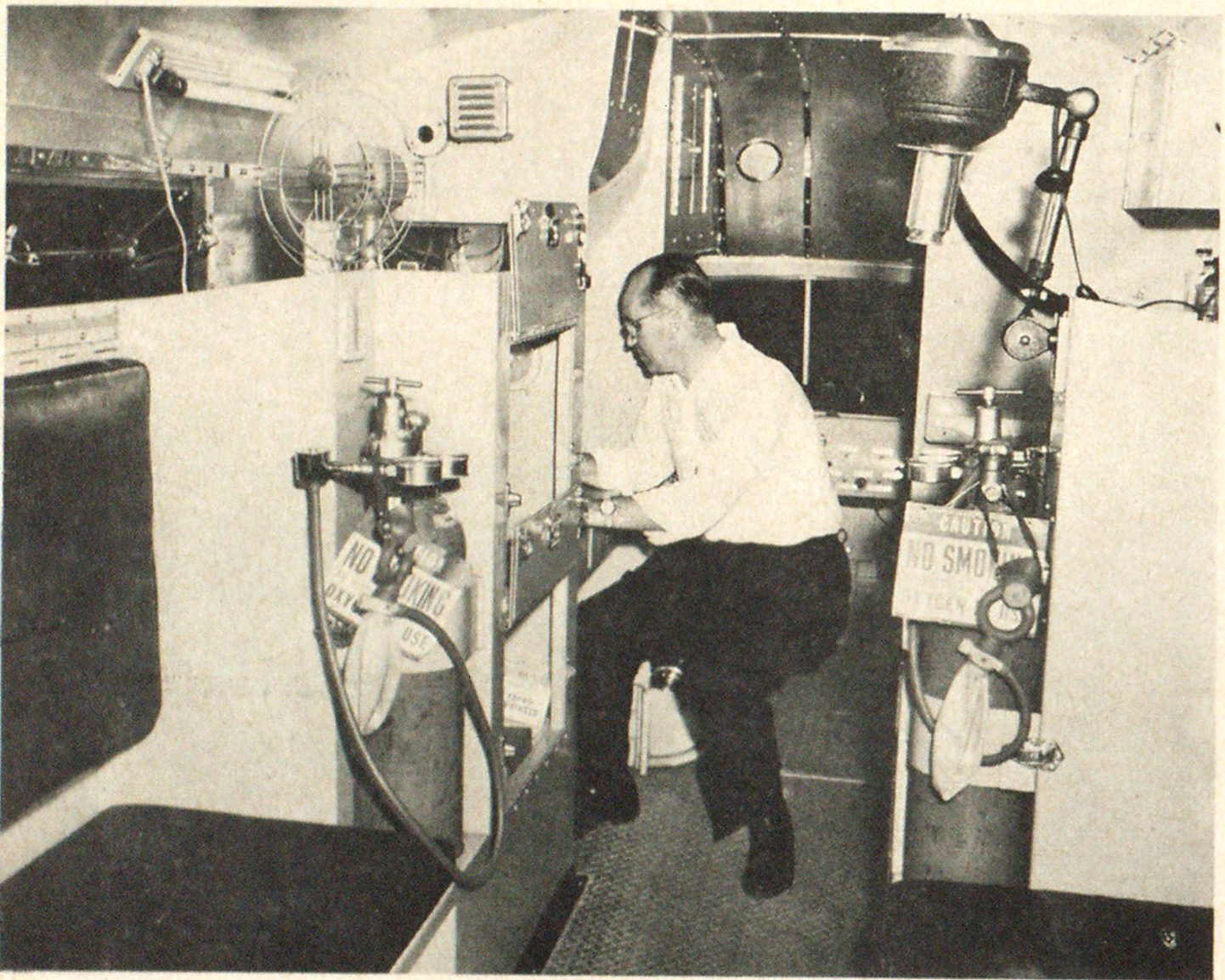 Interior of newly commissioned unit of the Rockville Centre Fire Department showing officer (Captain Boggs) on folding seat at control desk opposite dispensary counter and sink. Truck has running water, fans, drop seat and facilities for treating a number of patients at same time. Flood lights sink into compartments over control desk. Seats for driver and officer are in cab behind.