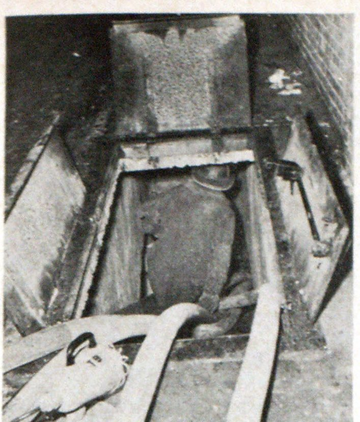 Chute through which entrance was made from rear of Terminal Building, north side, showing hose lines and spotlight illuminating opening. In this attack, illuminating equipment, breathing apparatus and protective fog patterns were a contributing factor to fire control.