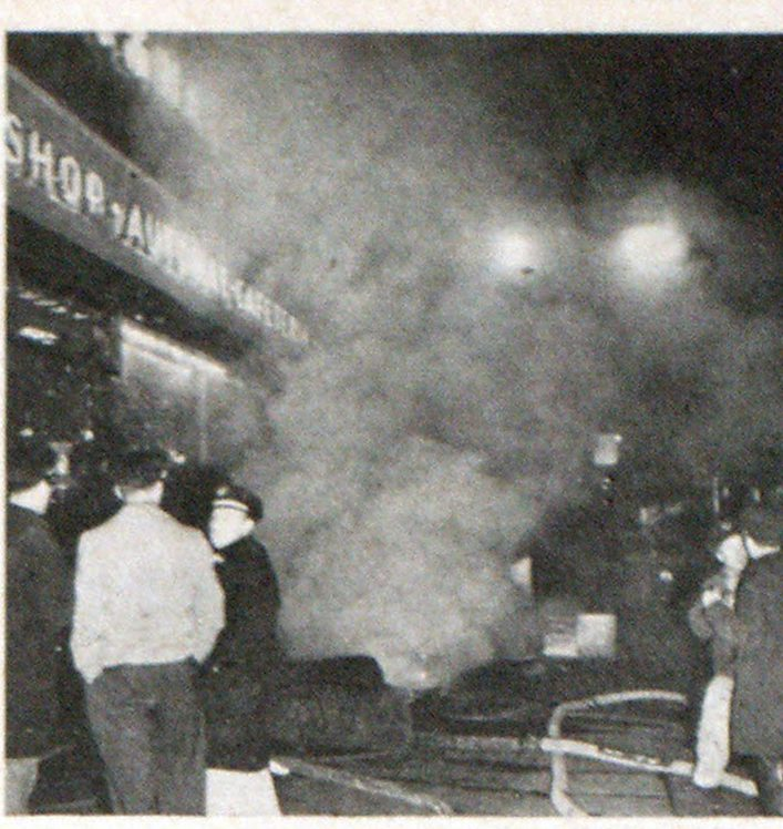 Every available street and sidewalk opening was used to vent contaminated sub-surface atmospheres. Here smoke ejectors and portable generators are used to vent below street-level areas. Scene is on Market street side.