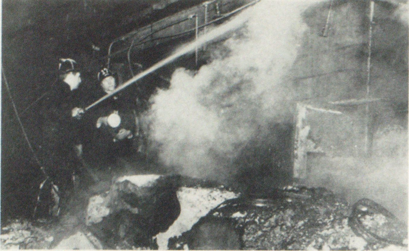 When explosion blew out wall of the Halby Company concrete block warehouse, one volunteer fireman was killed and several others injured. Here firemen operate inside the plant after the fire was controlled
