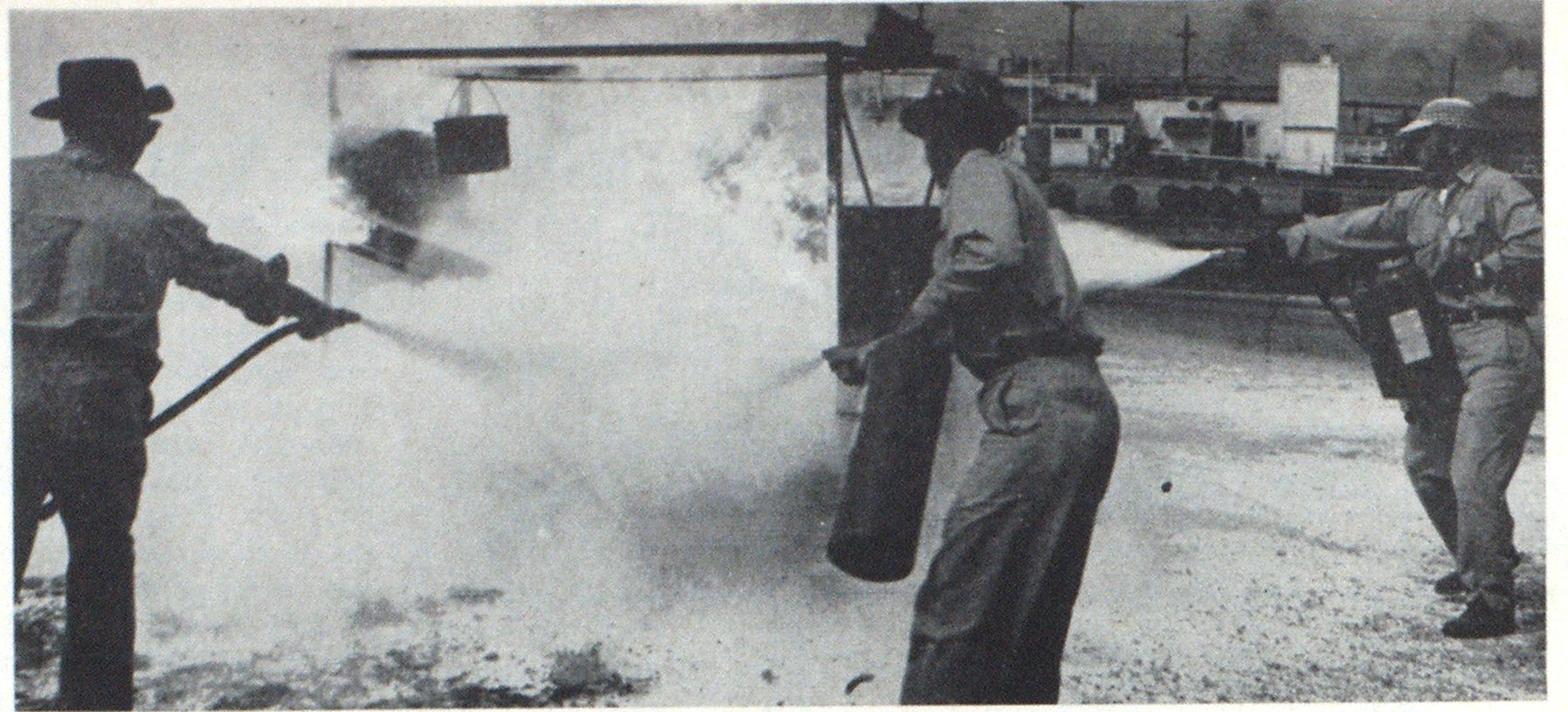 Three trainees attack a simulated industrial fire. The setup is designed to approximate fire in a dip tank