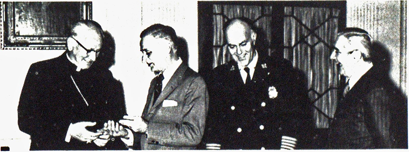 Newest chief, John Cardinal Krol of Philadelphia accepts an honorary chief's badge from John Gurash, chairman of the board of INA and chairman of the Philadelphia Fire Department Centennial Committee. Commissioner James J. McCarey is at extreme right and, in uniform. Deputy Commissioner William J. Eckles.