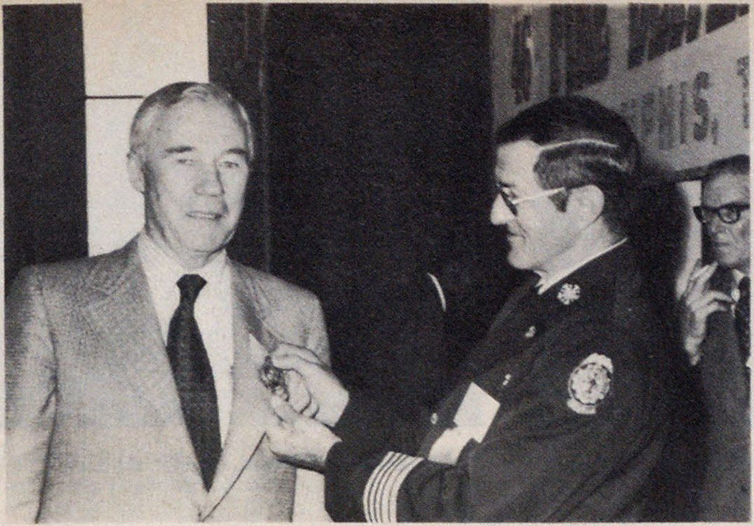 Honorary chief's badge is presented to James F. Casey, editor of Fire Engineering, by Chief Larry R. Williams of Memphis.
