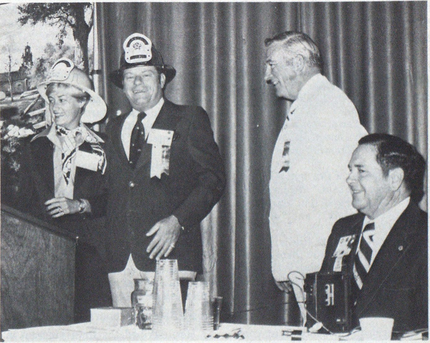 Presentation helmets are worn by Lieutenant Wilma Little, Montgomery County, Md , Fire and Rescue Services, and Past President David B. Gratz. Looking on are Fred Hornsby, standing, of Mine Safety Appliances, donor of the helmets, and President Myrle K. Wise.