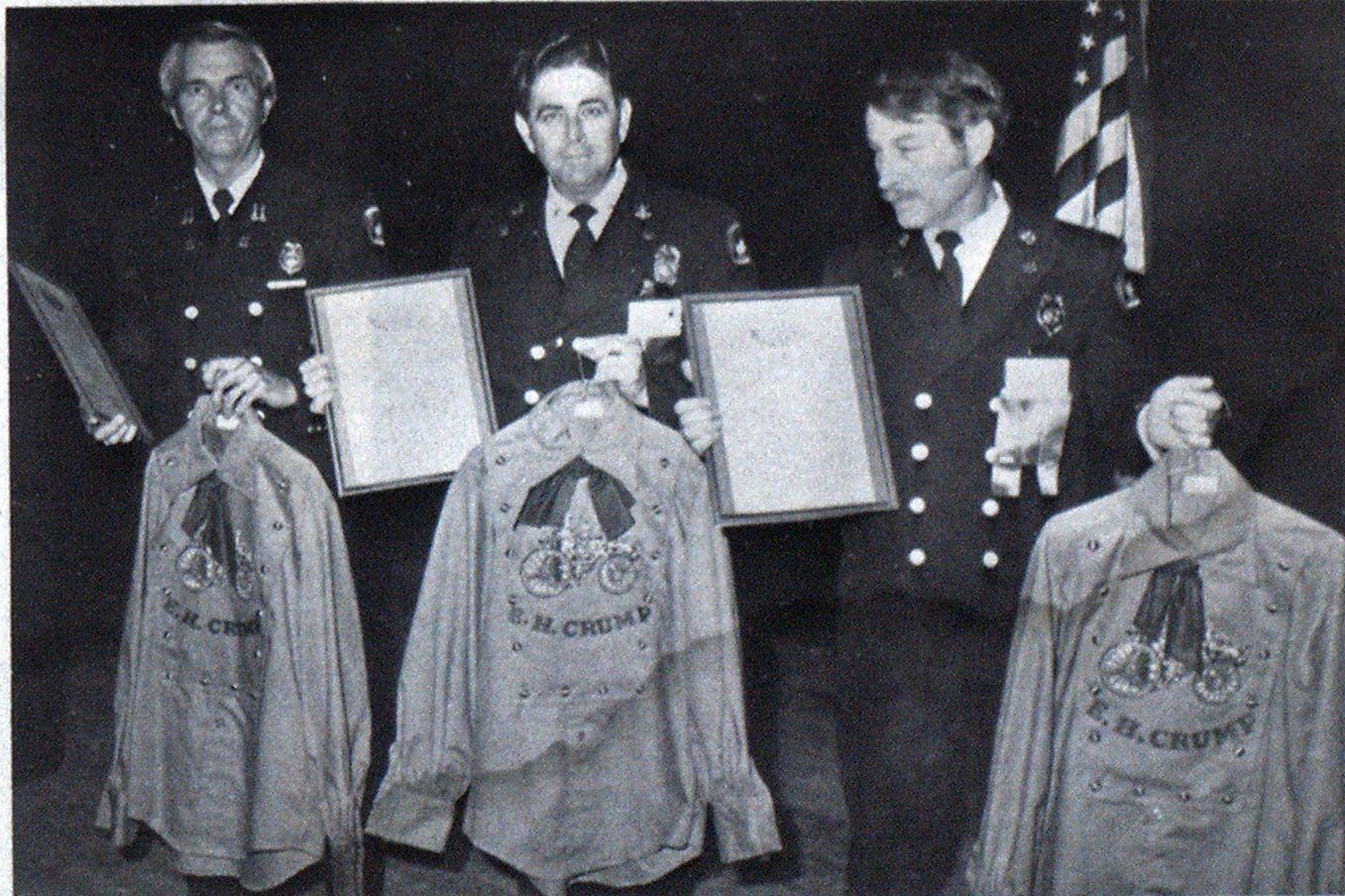 Old-style shirts are held by, from left, Captain Edward Xiques and District Chiefs D. G. Goolsby and A. O. Smith, Memphis Fire Department officers who helped display the old Memphis steamer, E. W. Crump, at a Missouri fire conference. The shirts were in appreciation of their work