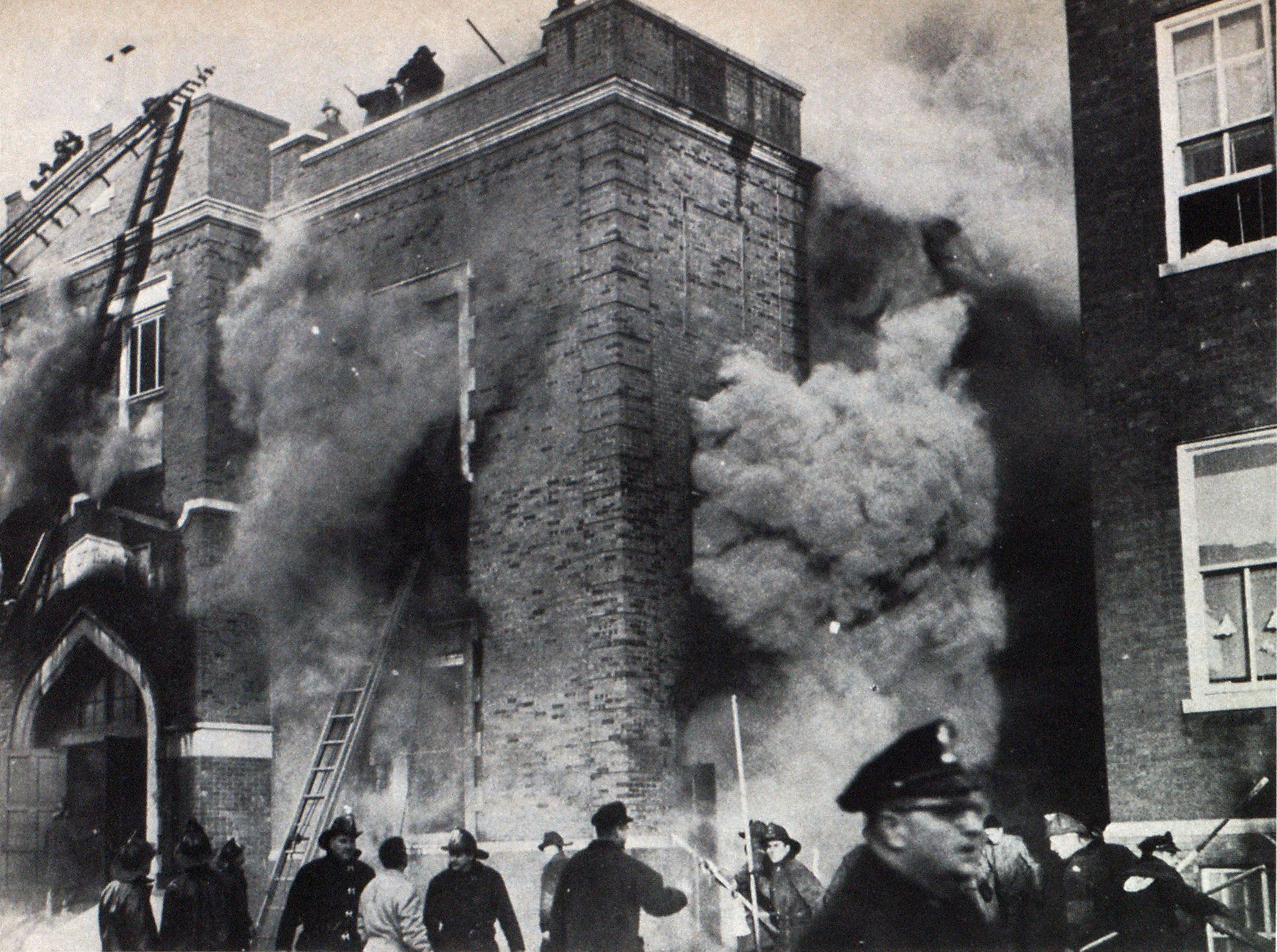Smoke pushes through windows of Our Lady of the Angeles School in Chicago during fire that killed 95 children and nuns