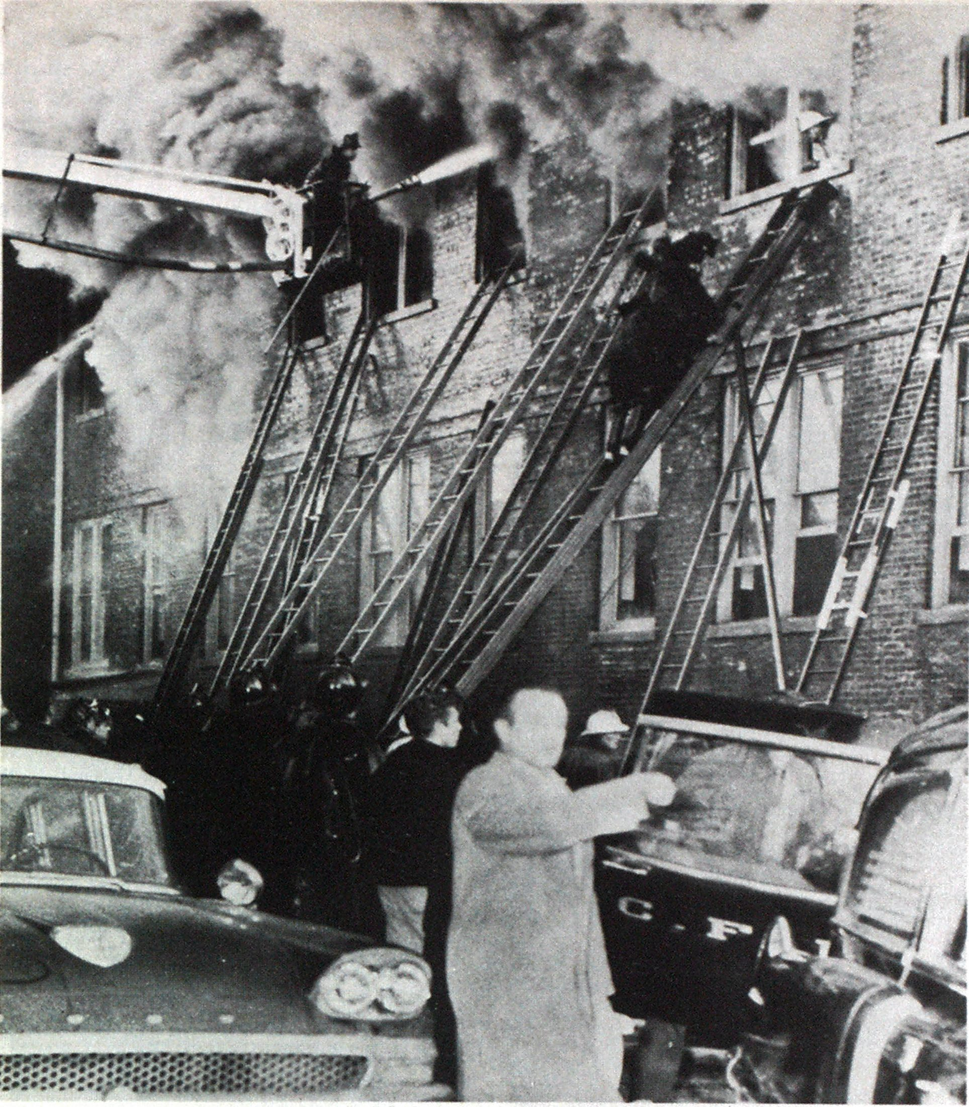 Early version of elevating platform is shown with turret pipe working at second-floor window of school. Note concentration of ladders at windows