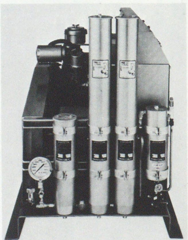 Purification cartridges may vary in number and size with system capacity. This particular unit uses three—two large and one small. The right-hand cylinder is the mechanical separator. Air flows from right to left.