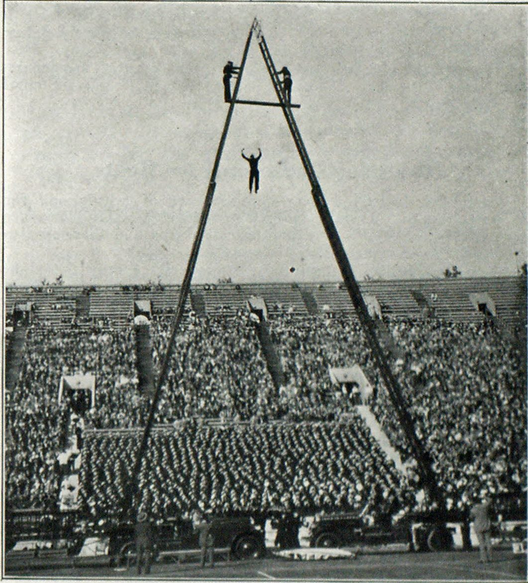 Los Angeles Firemen Show Skill at Annual Games Members of the Los Angeles, Cal., fire and police departments held their annual contests and games in the Coliseum to show their skill. The photograph shows a fireman dropping straight down from a height of one hundred feet into a fire net held by his comrades below. There was a good size crowd to watch the contests.