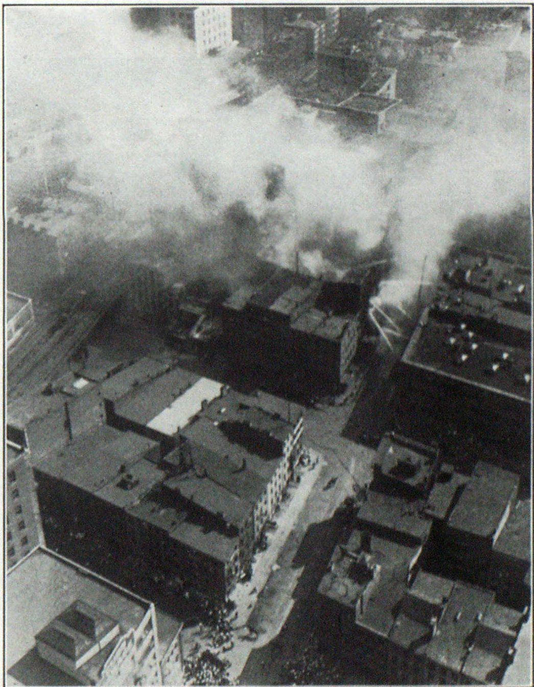Water Soaked Paper Displaced Wall at This Fire A few years ago, when the James Street, New York, warehouse burned, rolled paper on one of the floors expanded upon been wetted and forced a wall free of the ends of the floor beams, although the building was a reenforced concrete structure. This view is an aerial picture taken after the fire was under control.