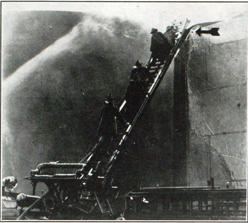 Bridgeport Firemen Fighting the Fire Caused by a Tank Explosion The arrow indicates where the iron worker was erfgaged in drilling holes in the tank when a short circuit caused a spark to ignite the fumes. The tank contained 80,000 gallons of gasoline.