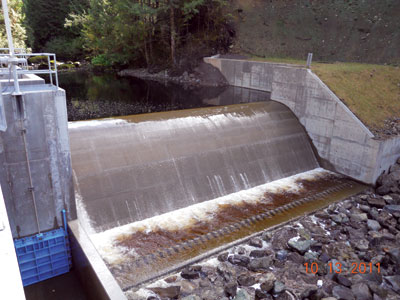 A 12-foot-long diversion weir impounds a 0.25-acre area of water, which is fed through an intake into a penstock that drops 920 feet in elevation to the powerhouse to provide flow up to 120 cubic feet per second.