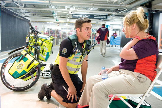 A bike medic tends to the needs of a patient at an Olympics venue.