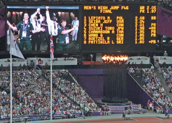 Paramedics celebrate success at the Olympic Stadium shown on a big screen.