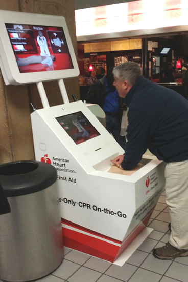 Medical Director Michael J. Reinhart, DO, FACEP, of the regional Emergency Health Services Federation in New Cumberland, Pa., performs CPR at an airport CPR kiosk.