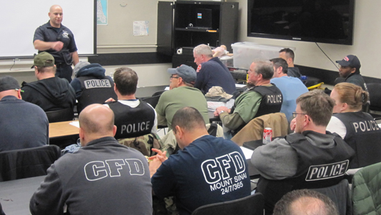 LEMART lead instructor Brian Berkowitz leads a debriefing session of CFD EMS personnel and CPD officers at the end of the simulation session.