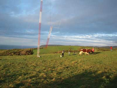 Workers lift segments of a wind monitoring station