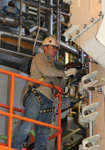 Drew Smith, machinist, performs maintenance on one of the Turk Plant's six coal pulverizers.