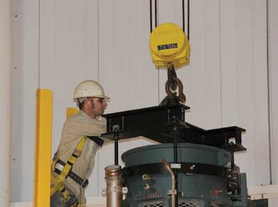 Joey White, machinist, works to move some of the Turk Plant's emissions control equipment into place.