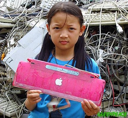Criança com produto Apple no meio de um lixo eletrônico